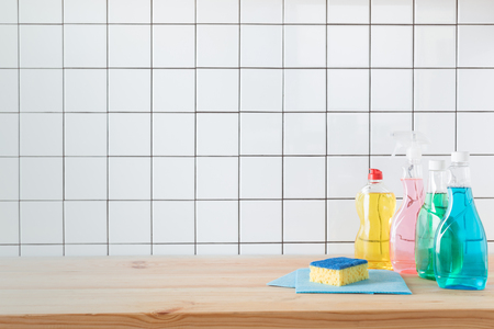 plastic bottles with colorful cleaning fluids, sponge and rags on tabletop    写真素材