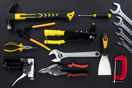 Top view shot of various reparement tools: wrenches, pliers, hammer, on black tabletop Stock Photo