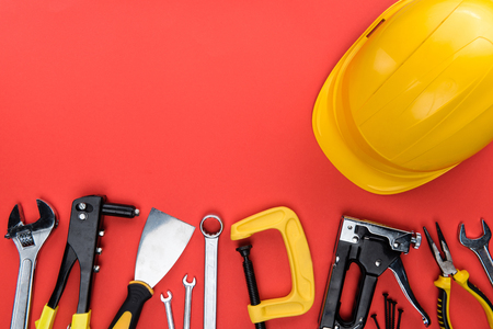 Top view shot of different reparement tools and hard hat, isolated on red