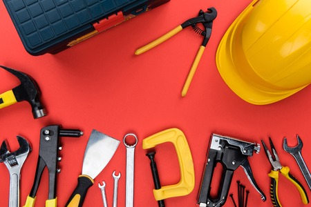 Top view shot of different reparement tools, toolbox and hard hat, isolated on red