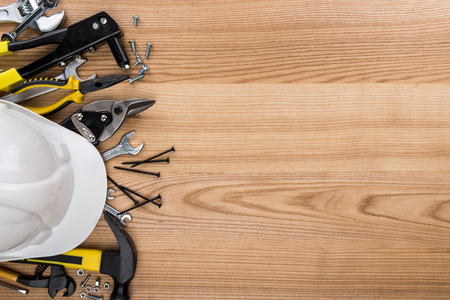 Top view shot of composition with various reparement tools and hardhat on wooden surface Stockfoto