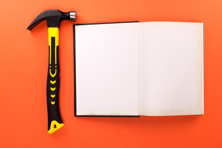 Top view shot of open book with blank pages and hammer on orange surface Stok Fotoğraf