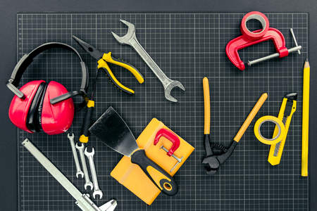 Top view shot of various reparement tools and ear muffs on graph paper