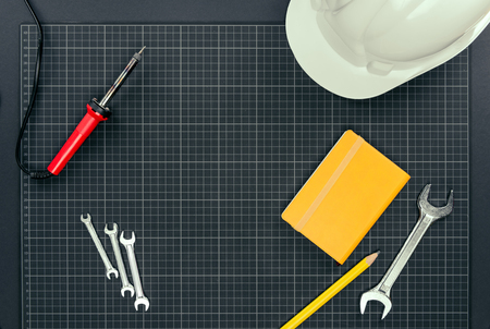 Top view shot of wrenches, soldering iron, notebook and hardhat on graph paper background