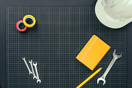 Top view shot of wrenches, tape, notebook and hardhat on graph paper background Stock Photo