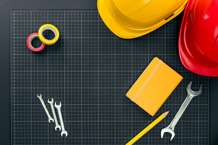 Top view shot of wrenches, tape, notebook and hardhats on graph paper background