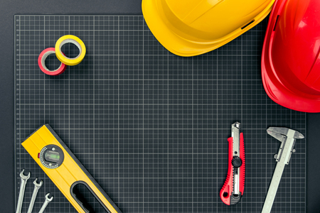 그래프 용지 배경에 정신 수준, 테이프, 수리 도구 및 hardhats의 상위 뷰 샷