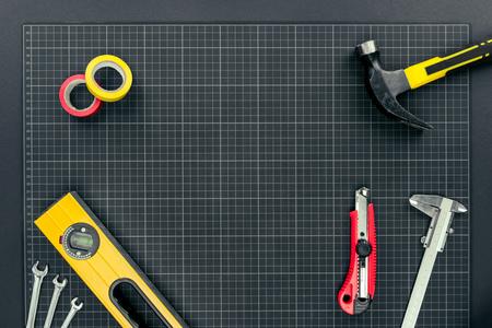 Bovenaanzicht shot van waterpas, tape, reparatie tools en hardhats op millimeterpapier achtergrond Stockfoto