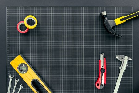 Top view shot of spirit level, tape, reparement tools and hardhats on graph paper background