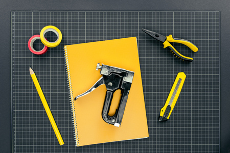 Top view shot of notebook, industrial stapler on graph paper