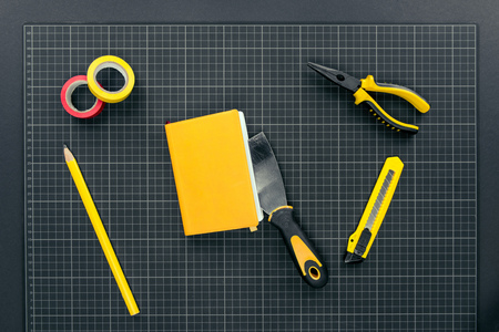 Top view shot of utility knife, spatula, notebook and pliers on graph paper
