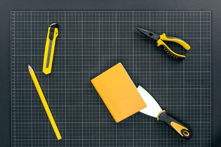 Bovenaanzicht shot van mes, spatel, notebook en tangen op millimeterpapier