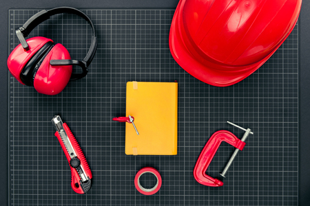 Top view shot of composition with various reparement tools, hardhat, ear muffs and yellow notebook on graph paper