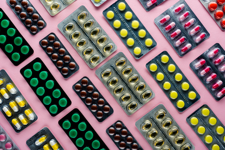 top view of various pills in blister packs on pink