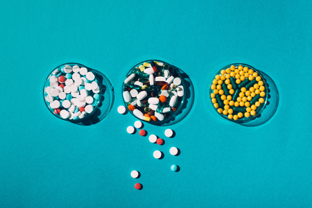 top view of various colorful pills in petri dishes on blue