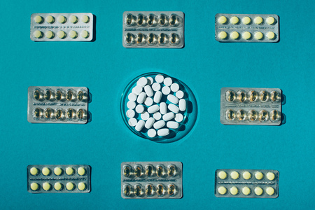 top view of various pills in blister packs and tablets in petri dish on blue Stock Photo