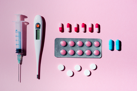 top view of medicine in blister pack, pills, thermometer and syringe on pink Фото со стока