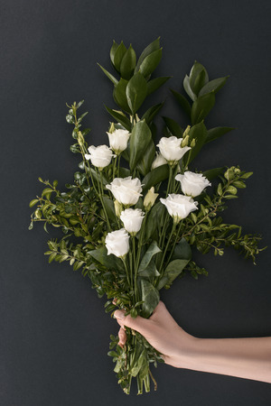 cropped image of female hand holding bouquet with eustoma and branches over black background