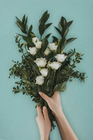 cropped image of female hands holding bouquet with eustoma flowers isolated on green