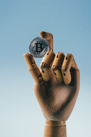 view of wooden puppet hand holding silver bit coin isolated on blue
