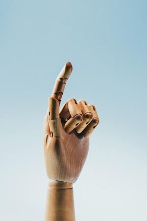 weergave van houten pop hand houden zilveren bit munt geïsoleerd op blauw