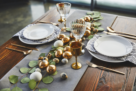 easter golden eggs, plates and glasses on table in restaurant Stock Photo