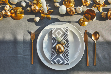 top view of golden egg and quail eggs on plates in restaurant, easter concept Standard-Bild - 98805287