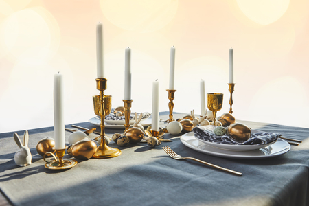golden chicken eggs and candles on festive table Stock Photo