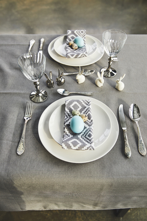 high angle view of painted blue chicken eggs on plates on table