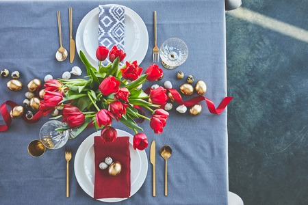 top view of bouquet of red tulips and easter eggs on festive table