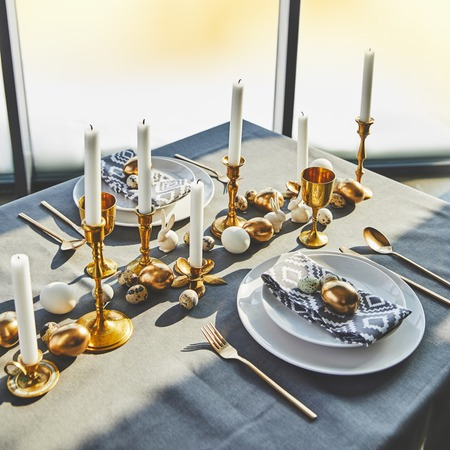 high angle view of easter eggs and candles on festive table with sunlight
