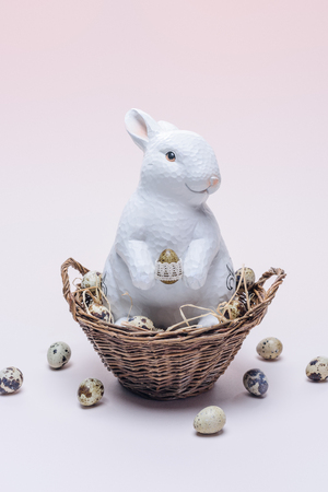 ester bunny with quail eggs and straw in basket on beige
