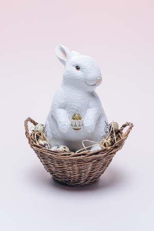ester rabbit with quail eggs and straw in basket on beige Stock Photo