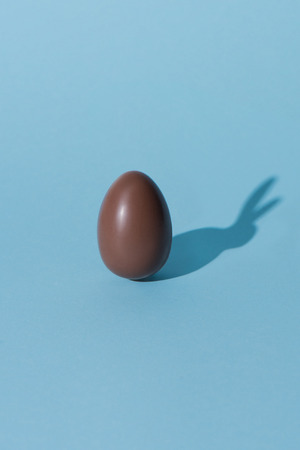 one chocolate easter egg with bunny shadow on blue surface Stock Photo