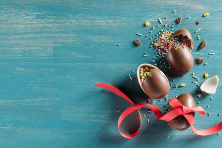 top view of broken chocolate easter eggs on turquoise surface