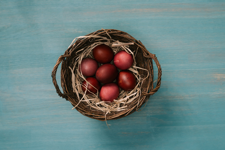 top view of easter basket with painted eggs and straw on table Stock Photo