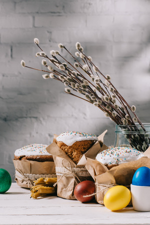 木製のテーブルの上にイースターパン、塗装卵、キャットキンとキャンドル
