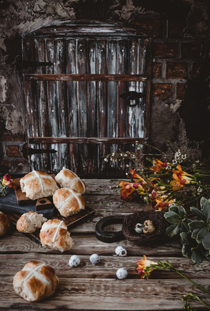 Easter table with hot cross buns and flowers