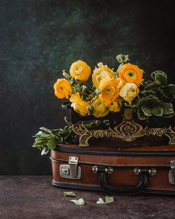 Ranunculus flowers bouquet on vintage suitcase