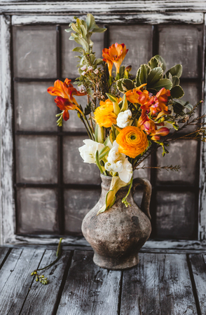 Ceramic jug with spring flowers on wooden table Stock Photo