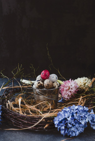 Colored quail eggs in nest with hyacinths on table