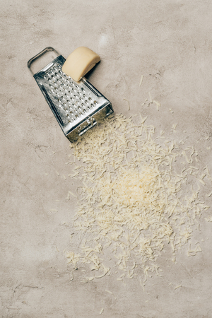Grater and piece of cheese on light background