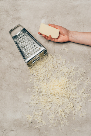 Close-up view of hand holding cheese by grater on light background Stockfoto