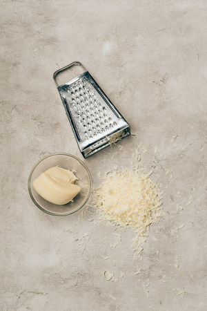 Grater and piece of cheese in bowl on light background