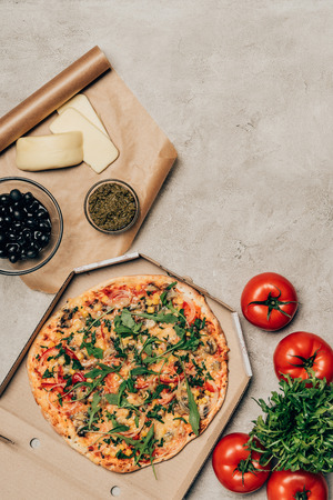 Whole pizza in cardboard box with tomatoes, cheese and olives on light background Archivio Fotografico