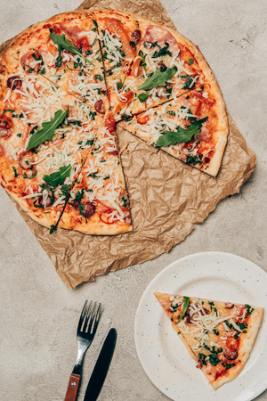 Pizza slice and whole pizza on light background