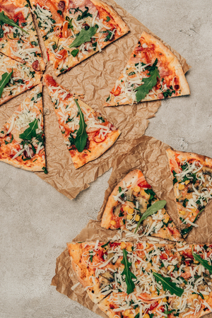 Slices of pizza with arugula on light background