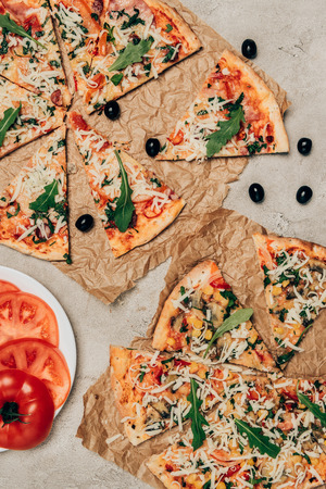 Slices of hot pizza and tomatoes on light background 版權商用圖片