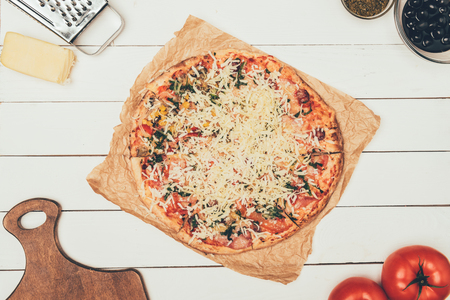 Pizza with cooking ingredients on white wooden background