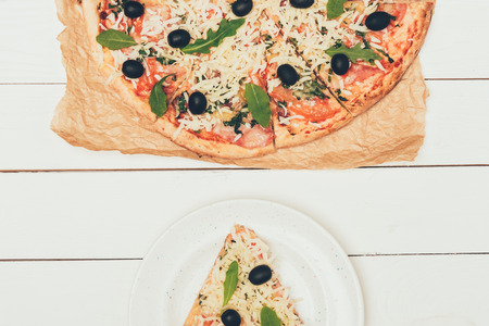 Pizza slice and whole pizza on white wooden background